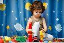 Mažas autistas berniukas žaidžia su kaladėlėmis